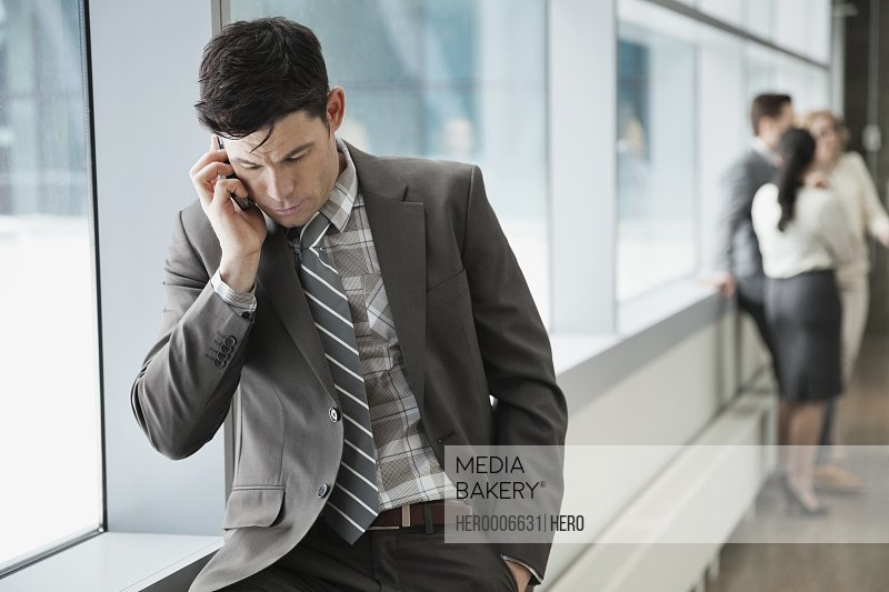 Businessman using mobile phone in office building