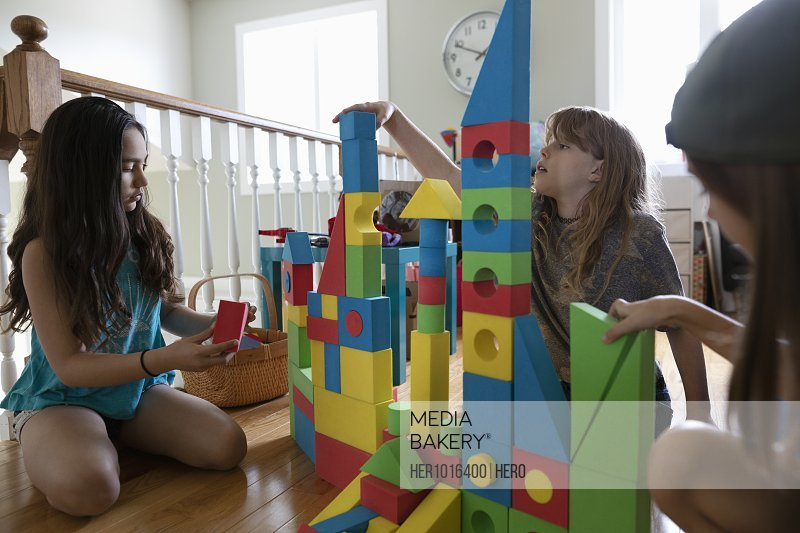 Girl friends playing with building blocks