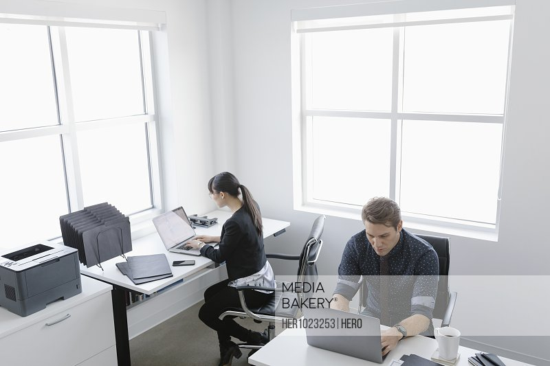 Business people working at laptops in shared office