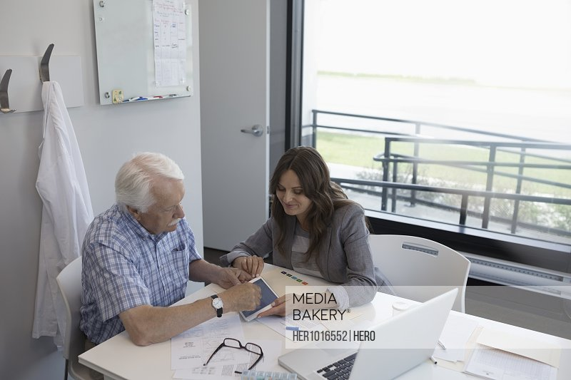 Female doctor showing digital tablet to senior male patient in clinic