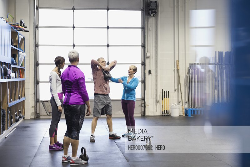 Coach instructing women using kettlebells in gym