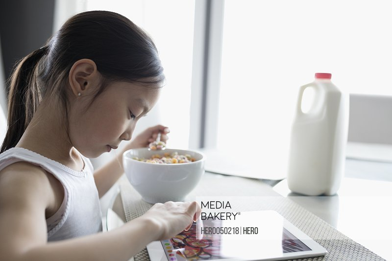 Girl eating cereal and using digital tablet at table