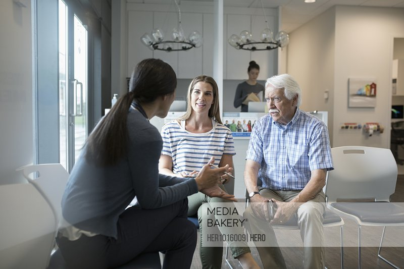 Female doctor talking with senior male patient and daughter in clinic waiting room