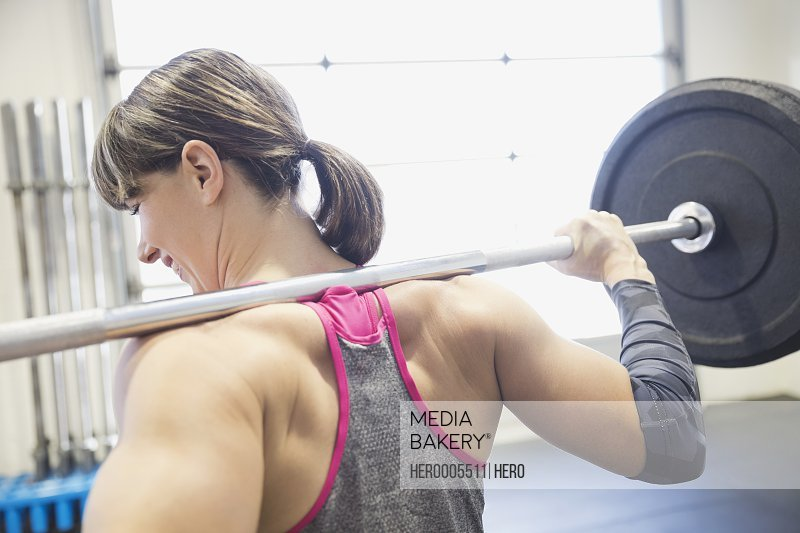 Woman standing with barbell on shoulders