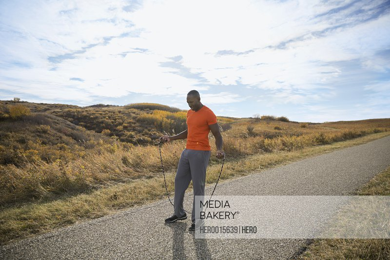 Man with jump rope on rural path