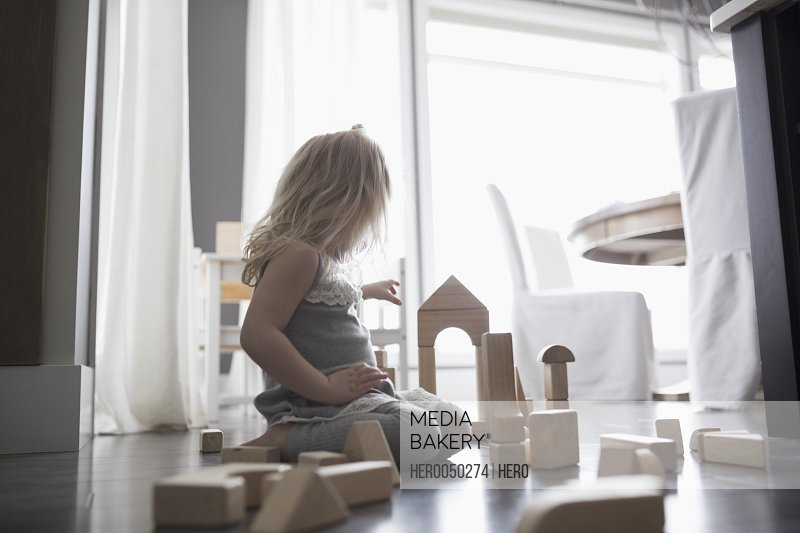 Girl playing with wood building blocks on floor