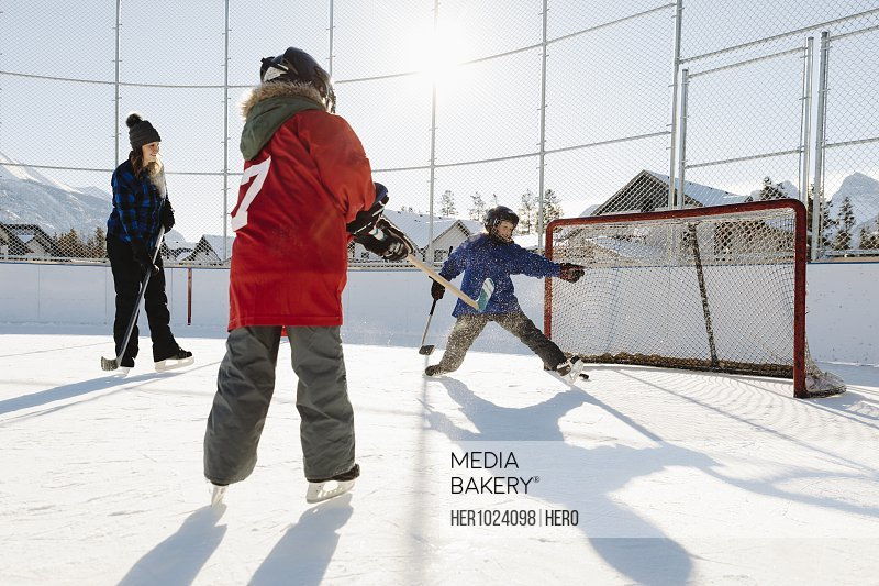 Family playing outdoor ice hockey