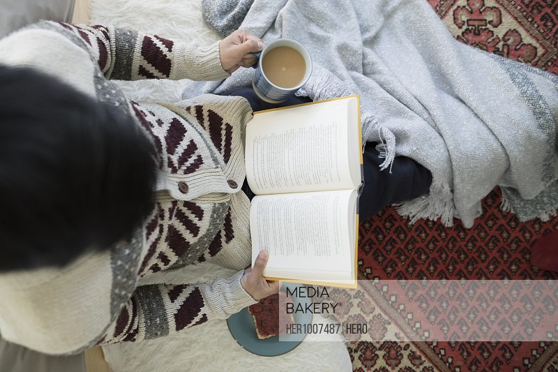 Overhead view man reading book, drinking coffee on floor
