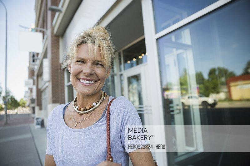 Portrait smiling blonde woman outside storefront