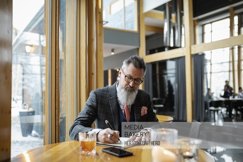 Fashionable hipster businessman with beard writing in notebook at restaurant table