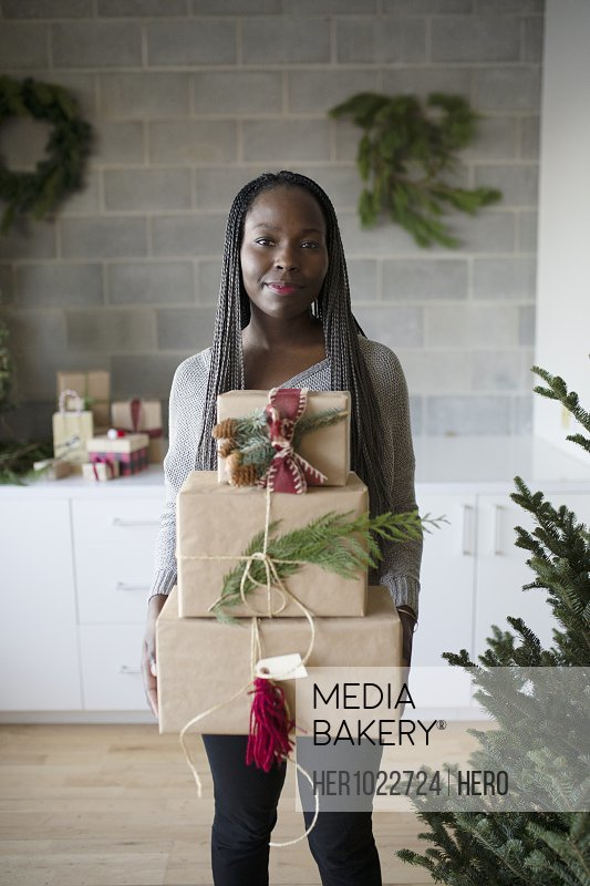 Portrait smiling young woman carrying stack of Christmas gifts