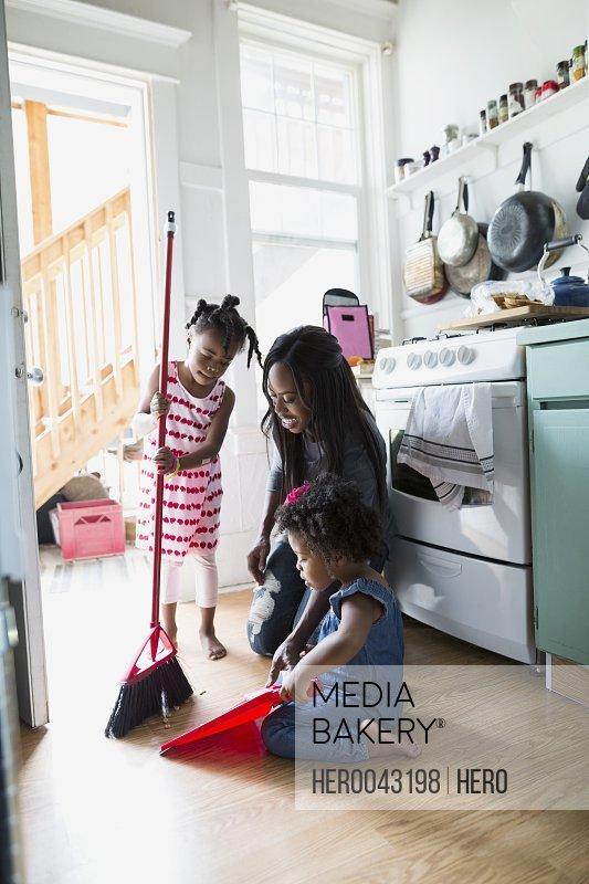 Daughters helping mother sweep kitchen floor