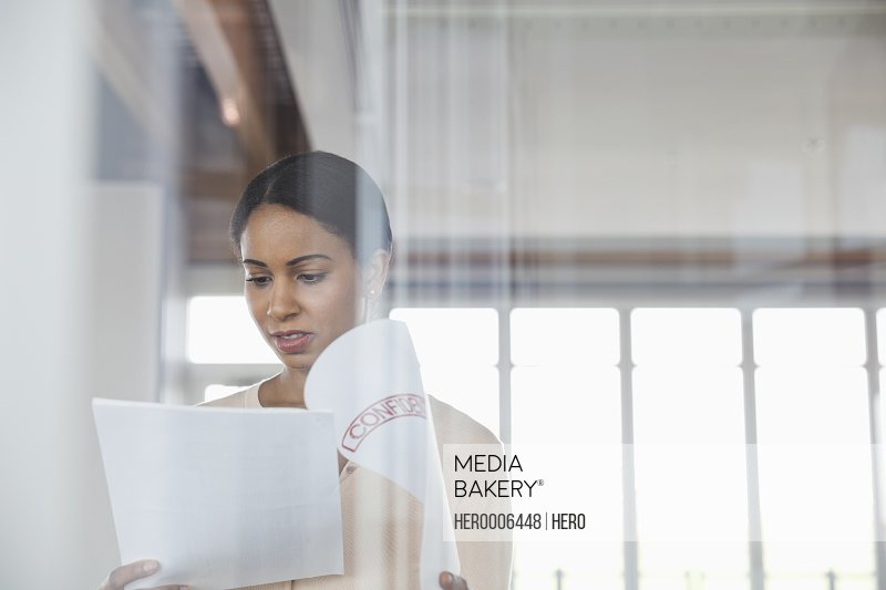 Businesswoman reading confidential documents in office