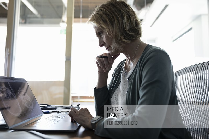 Serious female medical consultant working on laptop in office