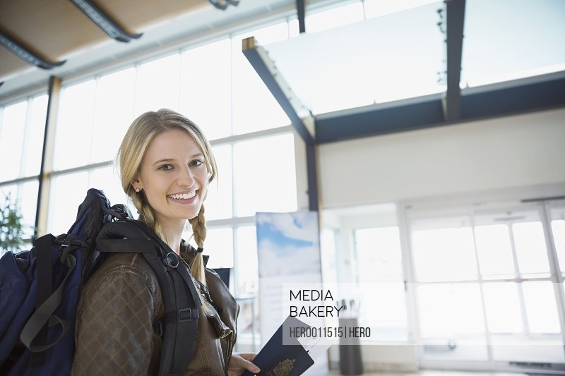 Portrait of smiling woman with backpack in airport