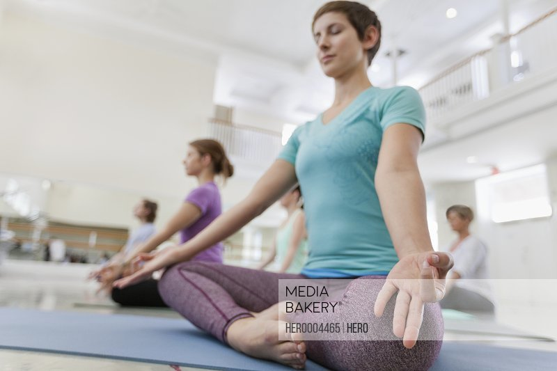 Group of people practicing lotus position in yoga studio