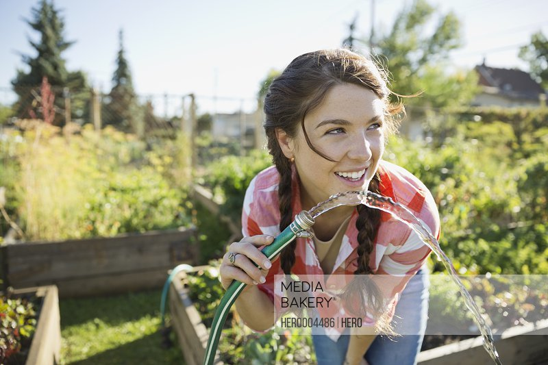 Woman drinking water from garden hose