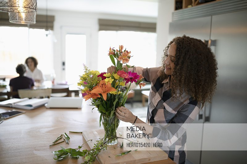 Teenage girl arranging flower bouquet in kitchen