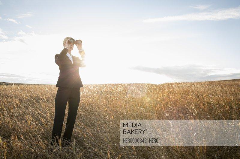 Businesswoman looking through binoculars outdoors