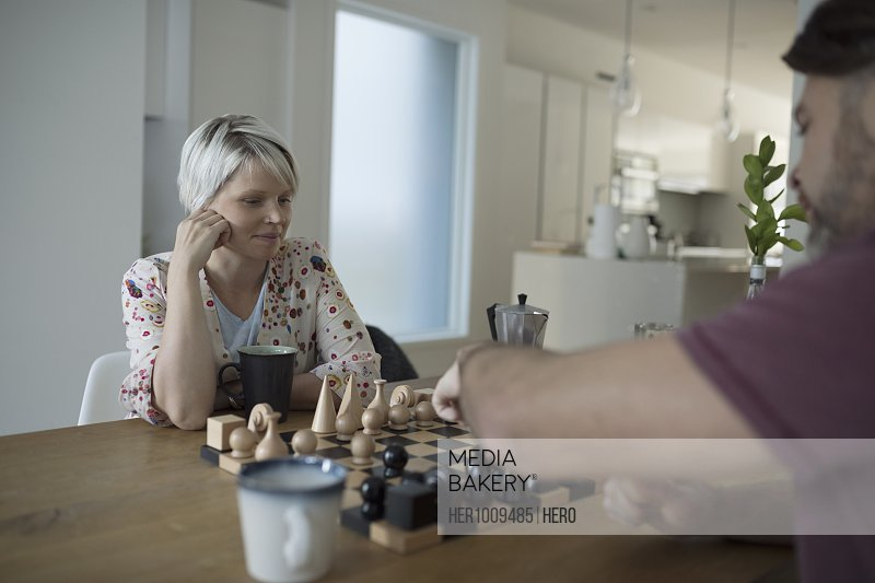 Couple drinking coffee and playing chess at table