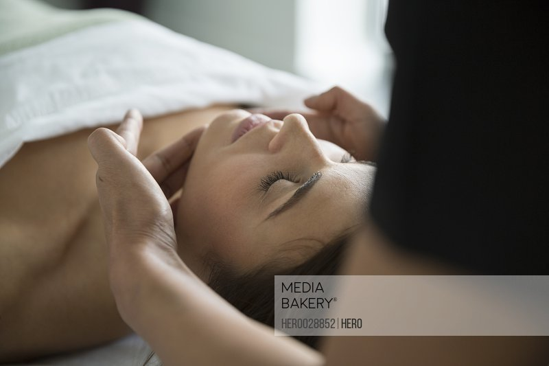 Serene woman with eyes closed receiving spa facial