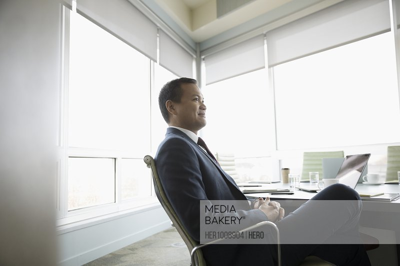Confident, attentive businessman listening in conference room meeting