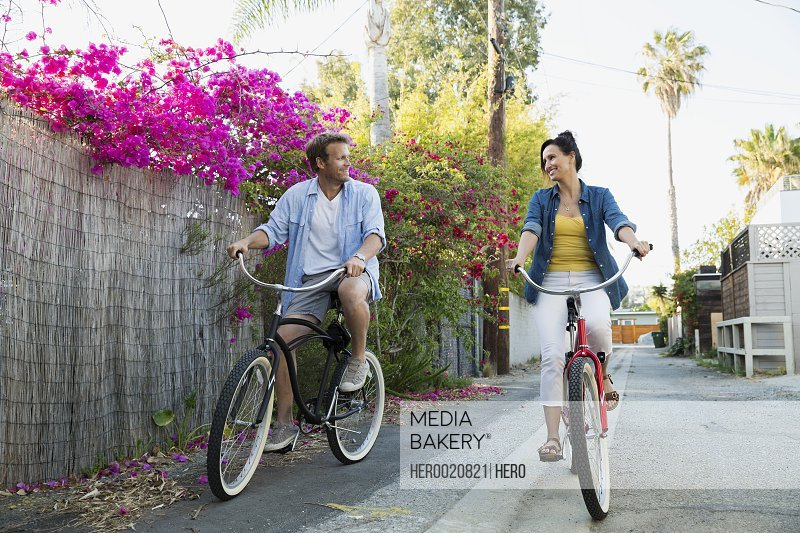 Couple riding bicycles in alley