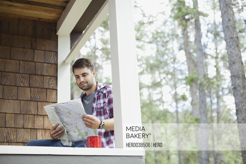 Young man sitting on cabin porch looking at map