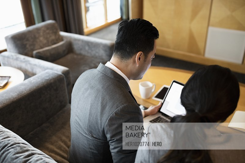 Business people using laptop in lobby