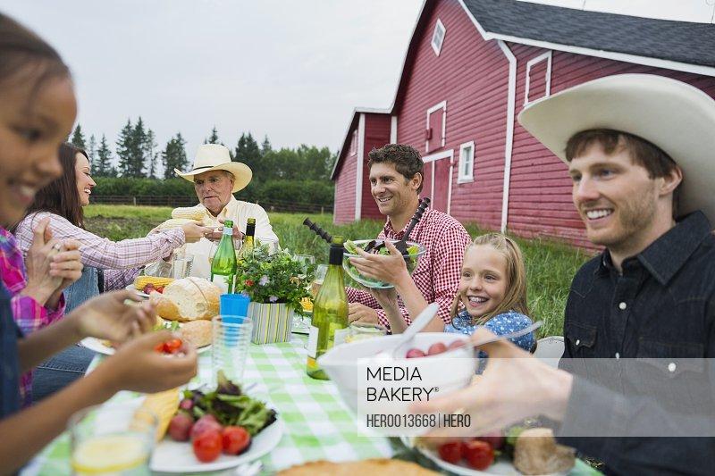 Multi-generation family enjoying dinner outside barn