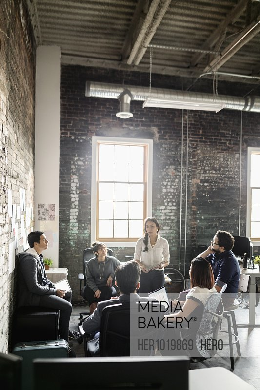 Creative businesswoman leading meeting in loft office