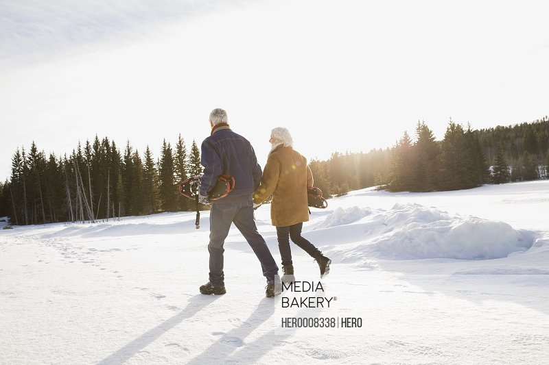 Couple carrying snowshoes outdoors