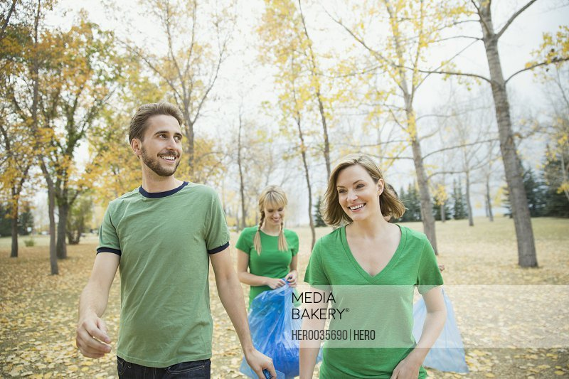 Volunteers walking in park with plastic bags