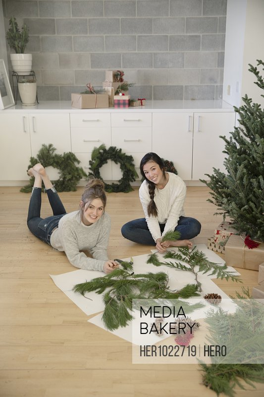 Portrait happy teenage girls making Christmas swags on floor