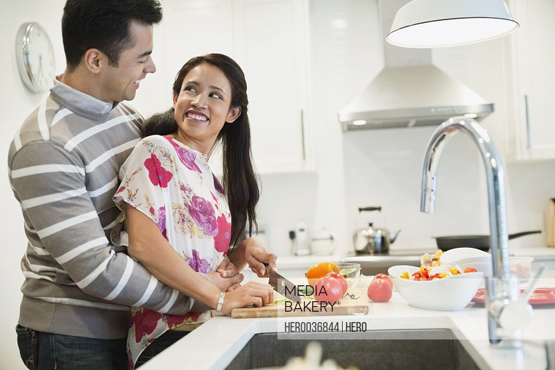 Romantic couple cutting vegetables at kitchen island