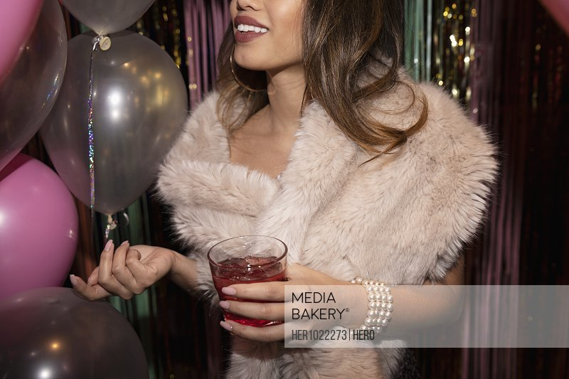 Young woman drinking cocktail at party