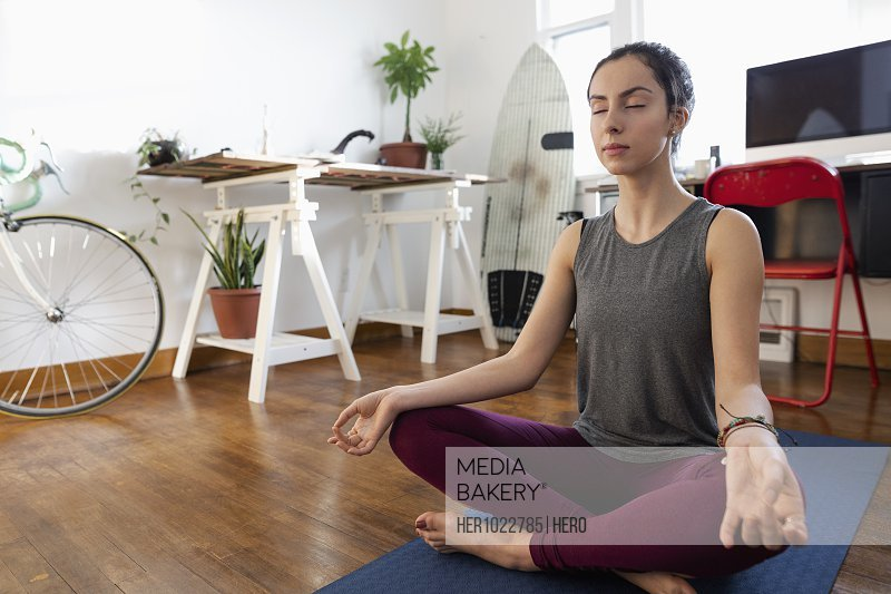 Serene young Latinx woman meditating on yoga mat
