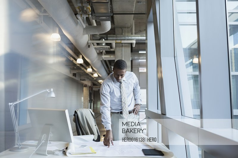 Businessman reviewing blueprint at office desk