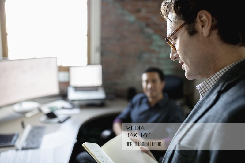 Creative businessman looking at journal in office