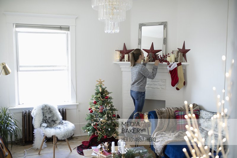 Young woman decorating living room for Christmas