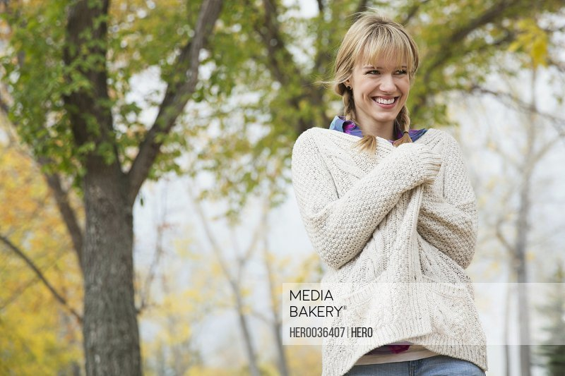 Woman wrapped in knit sweater in park