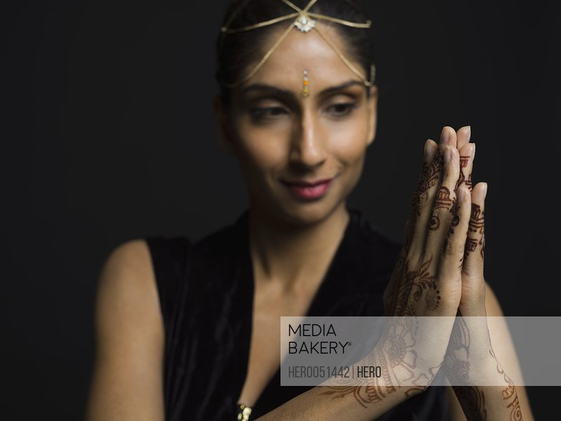 Portrait Indian woman with bindi and henna tattoos on clasped hands against black background