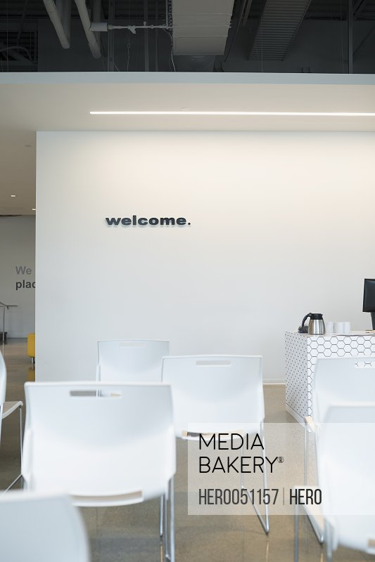 Welcome sign behind chairs in office lobby