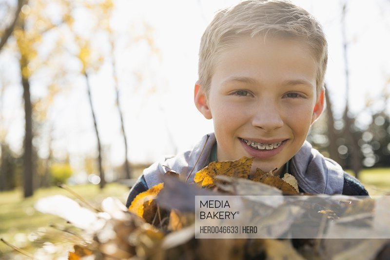 Portrait smiling tween boy with braces holding autumn leaves in sunny park