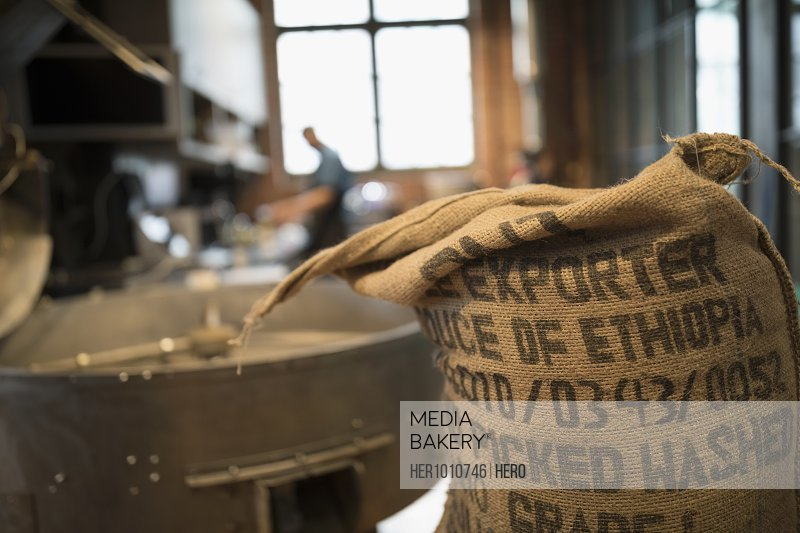 Burlap sack of Ethiopian coffee beans next to coffee roaster