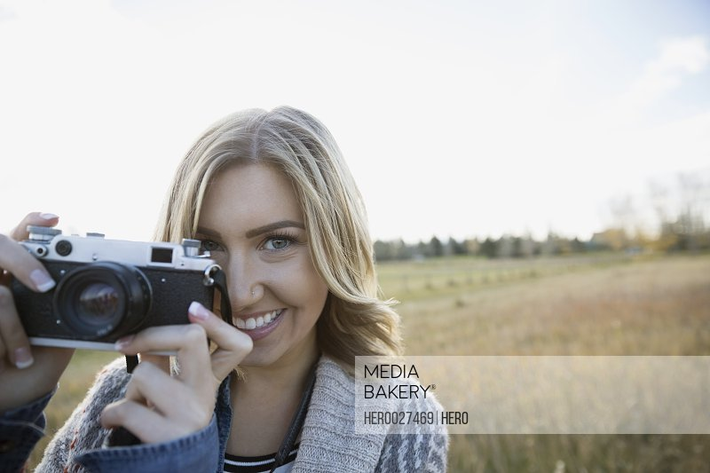 Portrait young woman using camera in sunny field