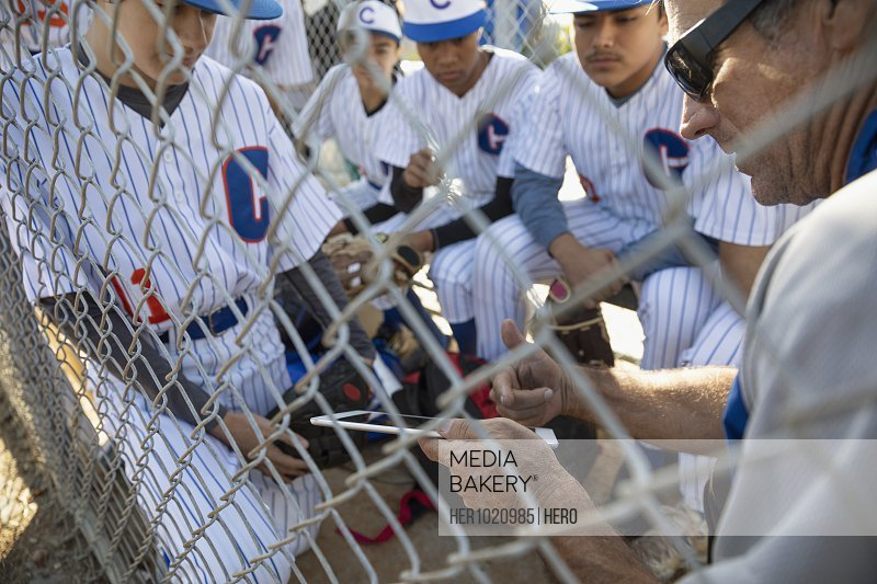 Coach with digital tablet talking to baseball team behind fence