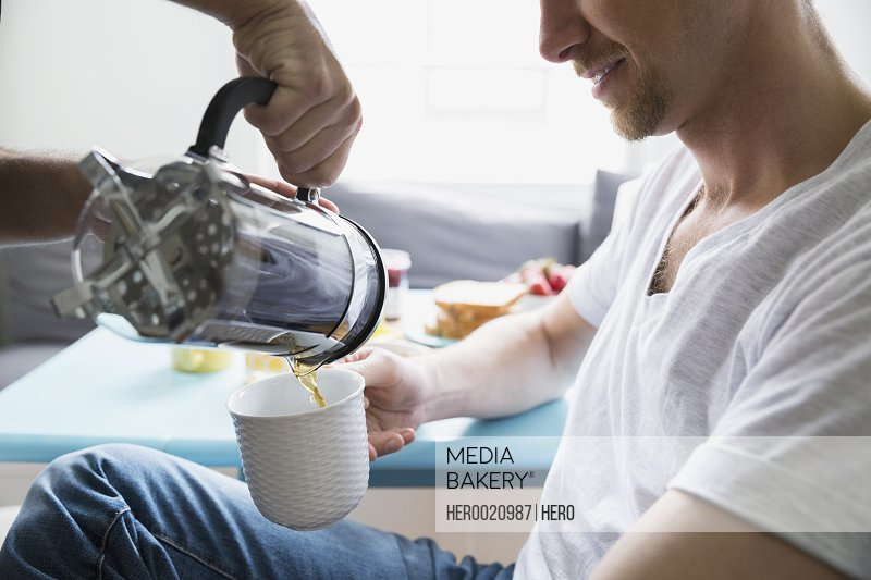 Man pouring French press coffee