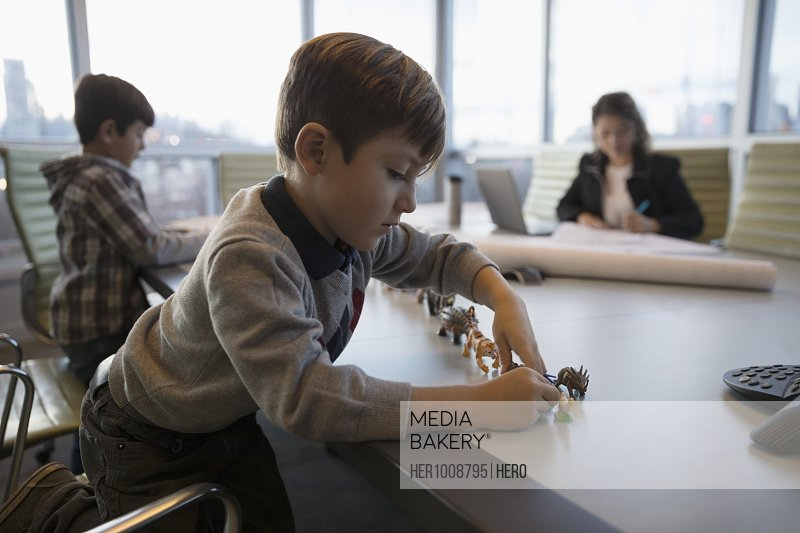 Boy playing with toys on conference room table with mother architect working in background