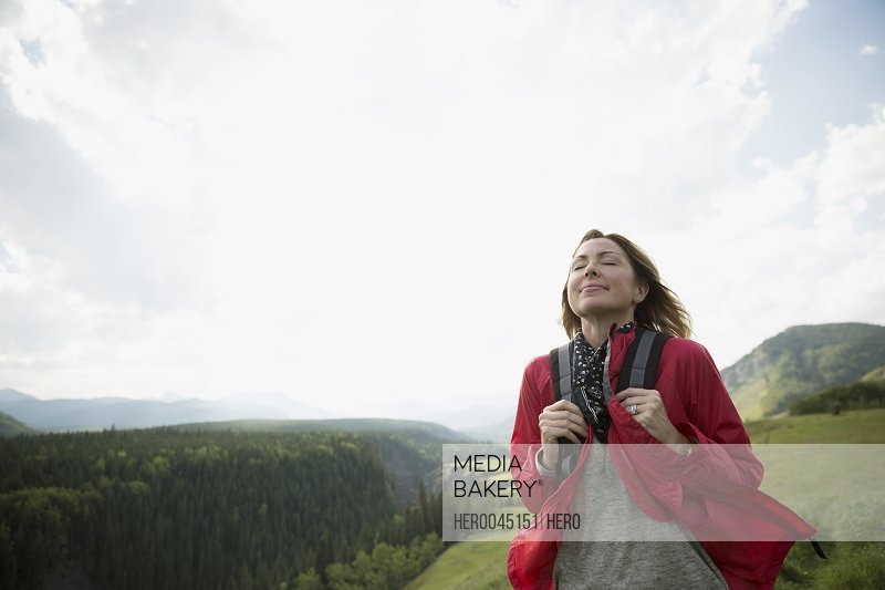 Serene woman with backpack hiking in remote rural field